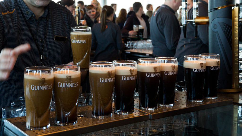 a bartender tapping multiple Guinness beers in a pub